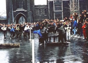 People outside in the winter watching the bed race obstacle course. Participants are pushing or riding on metal bed frames on wheels.