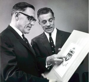 Two men looking at a picture of the newly-designed Innis College crest