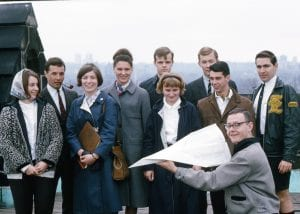 Smiling people posing for a photo, one person in front holding a large exam timetable folded into a paper airplane