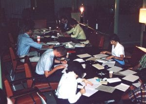 Many people sitting at a large table writing letters to incoming students.