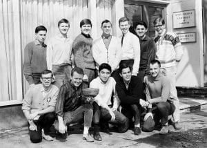 Men's Soccer team posing for a photo outside the Innis College Administrative Offices. One man is holding a deflated soccer ball.