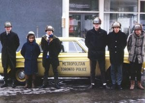Group of people in home-made helmets standing in front of a yellow Metropolitan Toronto Police car